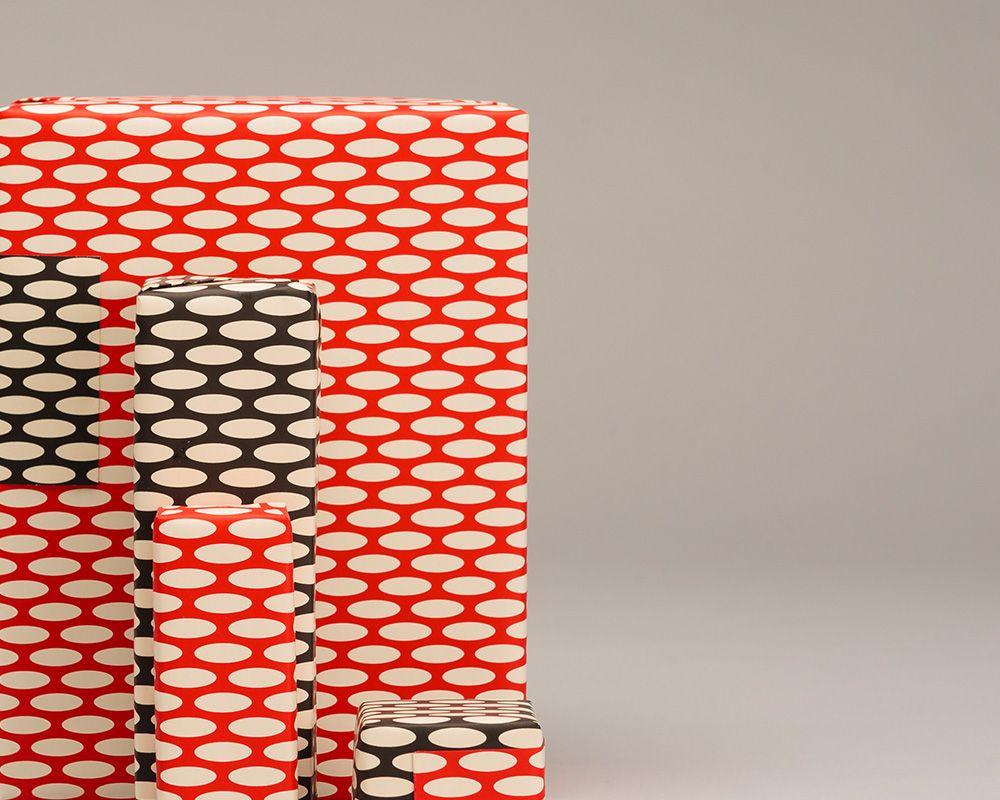 Papier Interpretation Geschenkverpackung rot und schwarz mit weissen Ellipsen